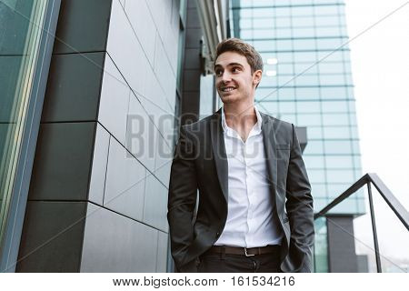 Business man in suit standing with arms in pockets near the office. From below image
