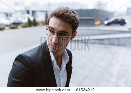 Business man in suit and glasses standing on the street