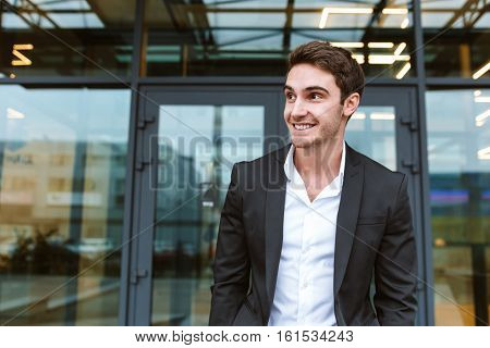 Young business man in suit standing near the office and looking aside