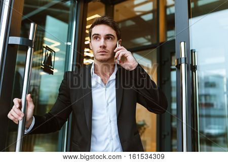 Serious business man in suit talking on phone in office and holding the door. From below image