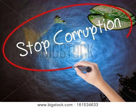 Woman Hand Writing Stop Corruption With Marker Over Transparent Board.