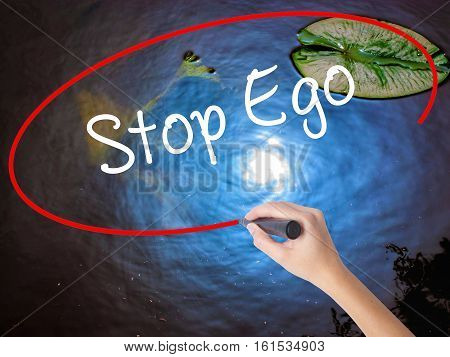 Woman Hand Writing  Stop Ego With Marker Over Transparent Board