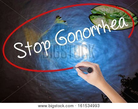 Woman Hand Writing Stop Gonorrhea With Marker Over Transparent Board.