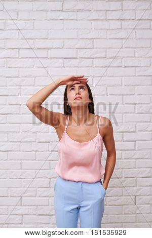 A mid shot of a cute woman having an eager look, holding one hand in the pocket. Lady wearing a silk rosy top