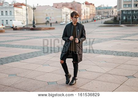 Stylish Guy With Glasses In Trendy Jacket And Torn Jeans With Black Sneakers In The City