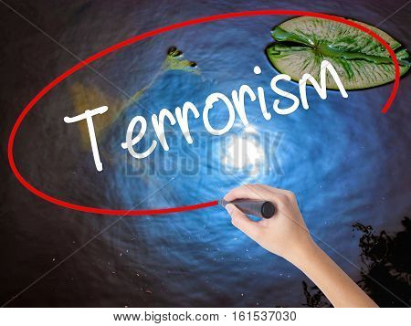 Woman Hand Writing Terrorism With Marker Over Transparent Board