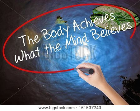Woman Hand Writing The Body Achieves What The Mind Believes With Marker Over Transparent Board