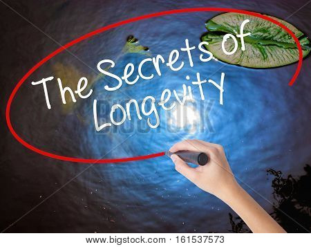 Woman Hand Writing The Secrets Of Longevity With Marker Over Transparent Board