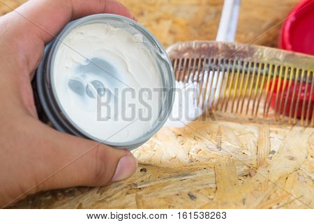 Pomade for hair styling with comb on wood background