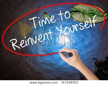 Woman Hand Writing Time To Reinvent Yourself With Marker Over Transparent Board