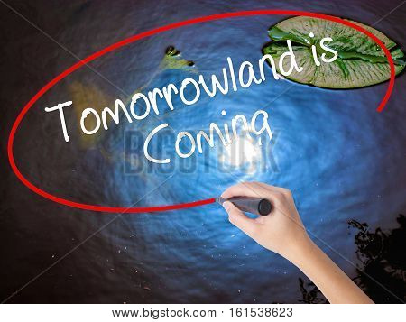Woman Hand Writing Tomorrowland Is Coming With Marker Over Transparent Board