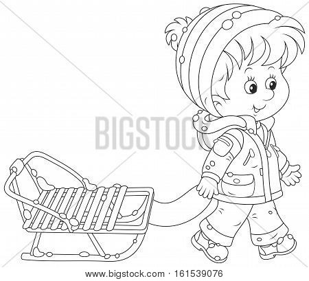 Little boy walking with his small sled