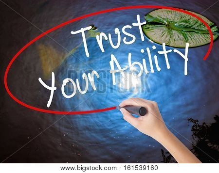Woman Hand Writing Trust Your Ability  With Marker Over Transparent Board