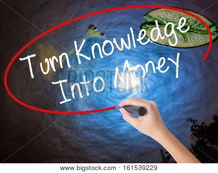 Woman Hand Writing Turn Knowledge Into Money With Marker Over Transparent Board