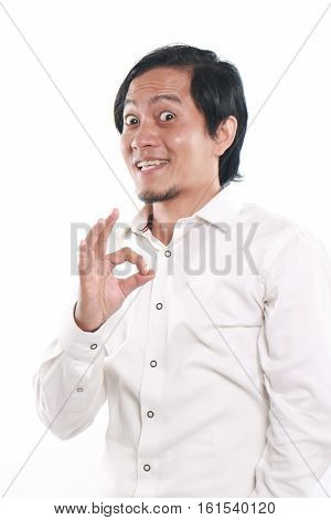 Photo image portrait of a cute funny young Asian man showing OK Sign with smiling face close up portrait over white background