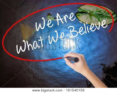 Woman Hand Writing We Are What We Believe With Marker Over Transparent Board