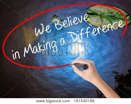 Woman Hand Writing We Believe In Making A Difference With Marker Over Transparent Board