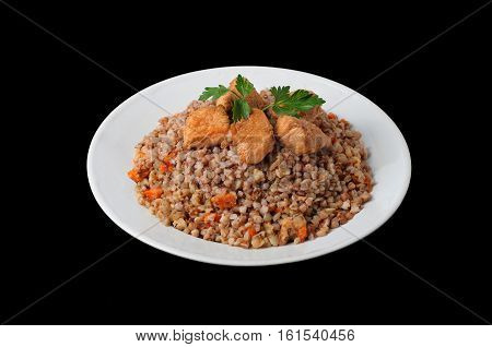 Healthy food. Buckwheat with meat and vegetables on white plate isolated on black