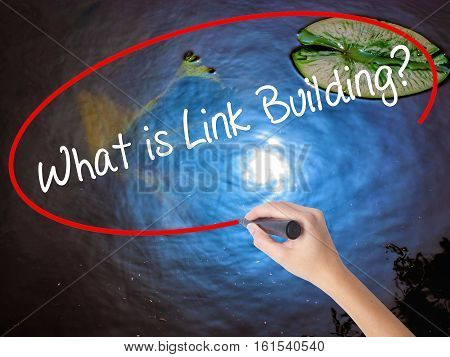 Woman Hand Writing What Is Link Building? With Marker Over Transparent Board