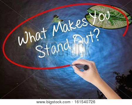 Woman Hand Writing What Makes You Stand Out? With Marker Over Transparent Board