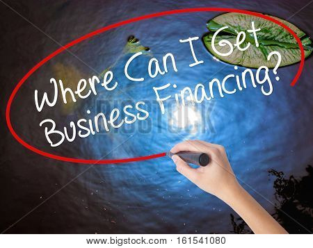 Woman Hand Writing Where Can I Get Business Financing? With Marker Over Transparent Board.