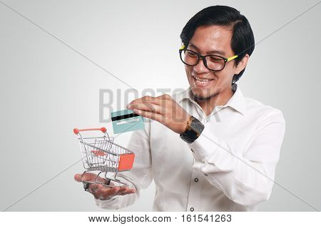 Photo image portrait of a funny young Asian businessman looking happy and smiling while putting a credit card into a small shopping trolley close up portrait consumer concept