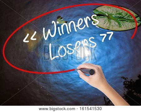 Woman Hand Writing Winners - Losers  With Marker Over Transparent Board