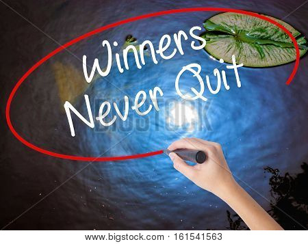 Woman Hand Writing Winners Never Quit With Marker Over Transparent Board