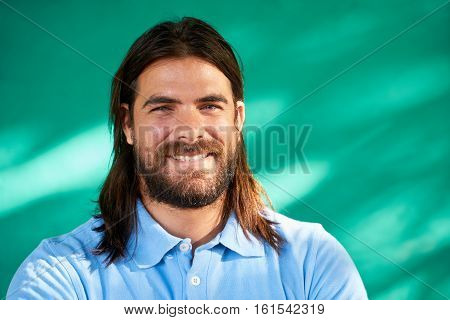 Real Cuban people and feelings portrait of happy young hispanic man with beard and long hair from Havana Cuba looking at camera and smiling