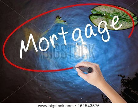 Woman Hand Writing Mortgage With Marker Over Transparent Board