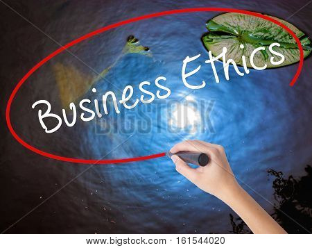 Woman Hand Writing Business Ethics With Marker Over Transparent Board