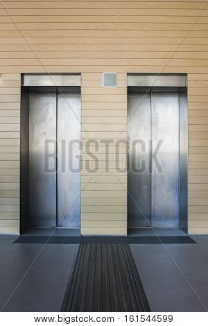 Front view of a modern elevator with closed doors in the lobby of a mall