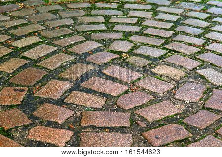 setts red and grey hewn stones laid on the road
