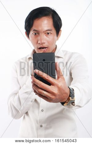 Photo image portrait of a funny young Asian man shocked while looking his smart phone. Holding phone with one hand while reading message on it over white background