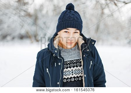 Handsome Young Man In Winter Jacket, Knitted Sweater With A Pattern And A Knitted Hat Walking In A W