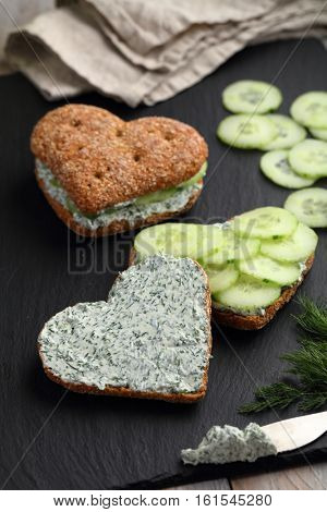 Two heart shaped sandwiches with cream cheese, dill, and sliced cucumbers on a slate board