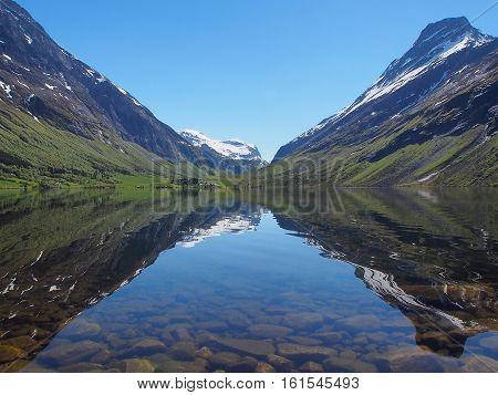Peaks reflecting in mountain lake like in a mirror Norway