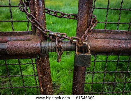 The Old And Rusty Lock On Metal Gate