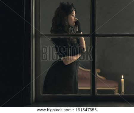 Sad Retro Victorian Woman In Black Dress Wiping Tear Standing Behind Window.