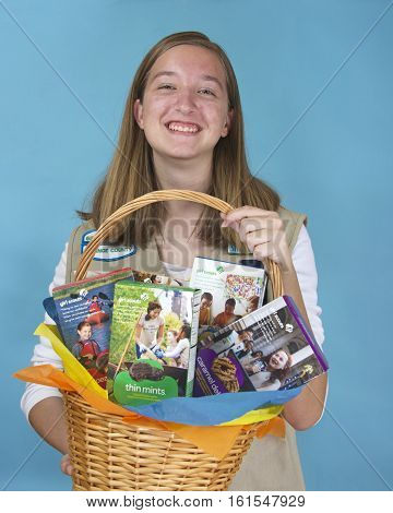 ALAMEDA CA - FEBRUARY 18 2016: Cadette Girl Scout Meaghan Fitzgerald holding Gift Basket with assortment of ABC Baker's brand Girl Scout cookie boxes. Girl Scout cookies only available once a year.