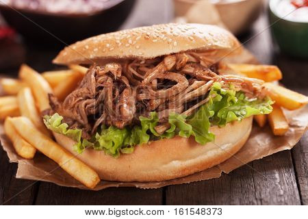 American pulled pork burger sandwich with french fries