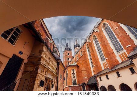 Church of St. Mary in the main Market Square on the background of dramatic sky. Basilica Mariacka. Krakow. Poland.