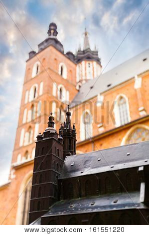 KRAKOW, POLAND - JULY 14, 2016: Church of St. Mary in the main Market Square with a miniature replica in bronze in the foreground. Basilica Mariacka. Krakow. Poland.