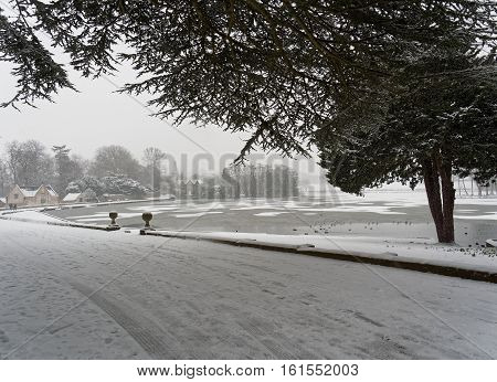 Winter scene settled and falling snow by Melbourne Pool Melbourne Derbyshire England.