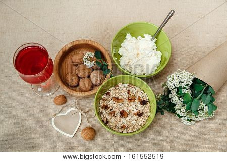 Healthy Organic Breakfast.Walnuts,Oatmeal and Cottage Cheese.Green Ceramic and Wooden Plates.Glass with Red Drink.Wish Heart Card with Bouquet.
