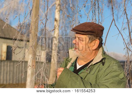 Outdoor portrait of a bearded Ukrainian peasant standing under birch tree at fall season