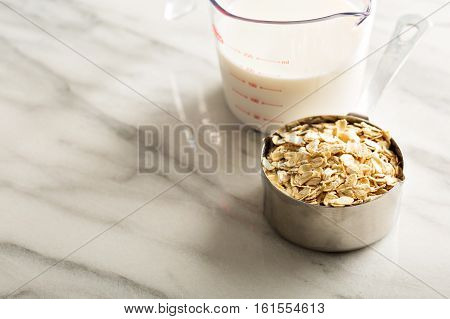 Cooking oatmeal with oats in a measuring cup and milk