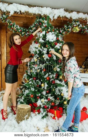 Mother and beautiful daughter decorating Christmas tree