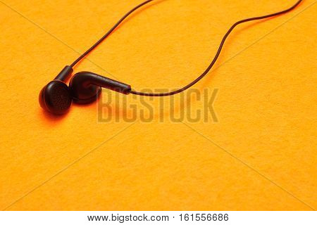A pair of earphones isolated against a yellow background