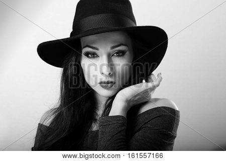 Sexy female model with bright makeup and red lipstick in black hat posing. Closeup fashion portrait. Black and white. Art